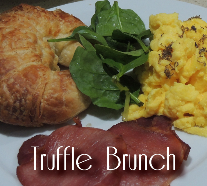 Photo of a truffled brunch of scrambled eggs, spinach, bacon and a croissant