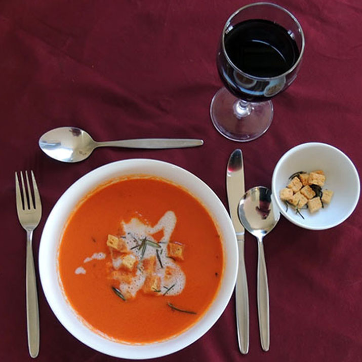 Photo of a soup entree including croutons and a glass of wine
